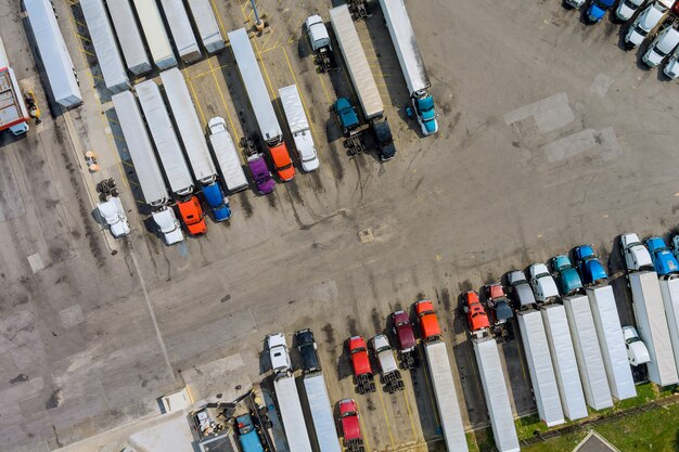 Il parcheggio per auto con vista aerea superiore per i camion pesanti si ferma nell'area di sosta nell'autostrada i camion stanno in fila