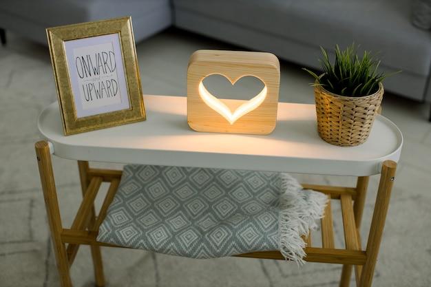 Vista dall'alto di decorazioni per la casa fatte a mano, tavolino da caffè con cornice per foto, lampada decorativa in legno con foto di cuore e pianta verde in vaso di fiori di vimini.