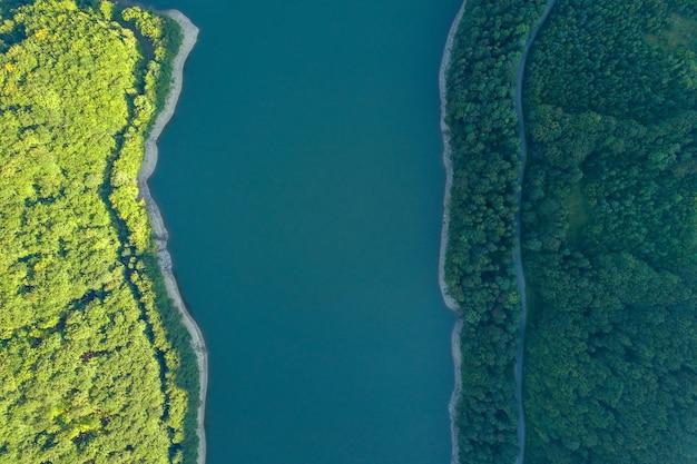 Vista aerea dall'alto verso il basso del grande lago con acqua cristallina tra le colline di alta montagna ricoperte da una fitta foresta sempreverde