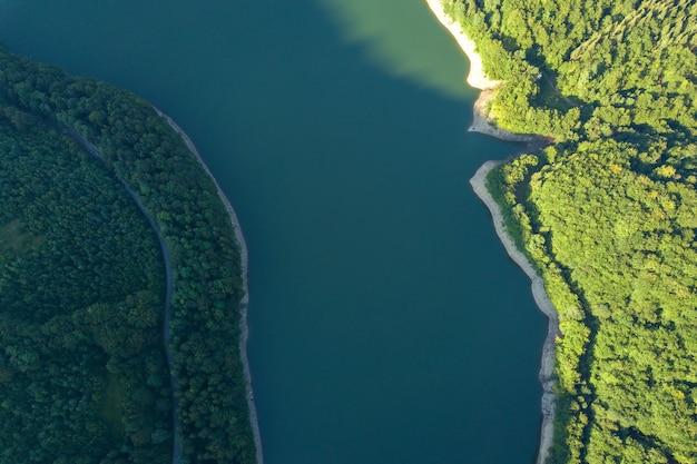Vista aerea dall'alto verso il basso del grande lago con acqua cristallina tra alte montagne high