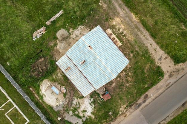Vista aerea dall'alto in basso di una casa di mattoni con telaio del tetto in legno in costruzione