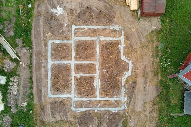 Vista aerea dall'alto verso il basso dei lavori di costruzione delle fondamenta in calcestruzzo della nuova casa in cantiere.