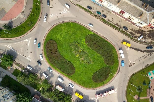 Vista aerea dall'alto verso il basso dell'intersezione della rotonda di una strada trafficata con traffico di auto in movimento