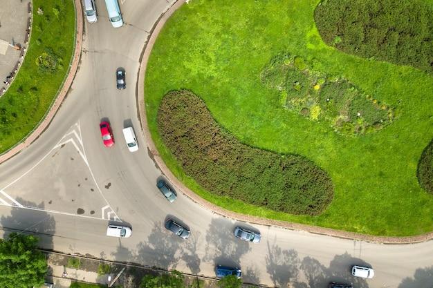 Vista aerea dall'alto verso il basso dell'intersezione della rotatoria di una strada trafficata con traffico di auto in movimento.