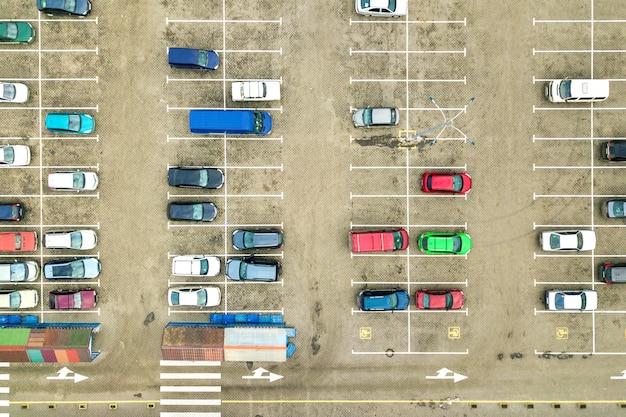 Vista aerea dall'alto verso il basso di molte auto in un parcheggio di un supermercato o in vendita sul mercato del concessionario auto.