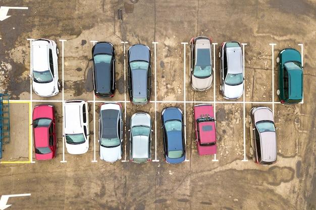 Vista aerea dall'alto in basso di molte auto in un parcheggio di un supermercato o in vendita sul mercato del concessionario auto