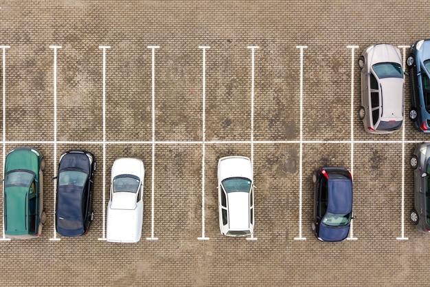Vista aerea dall'alto verso il basso di molte auto in un parcheggio del supermercato o in vendita sul mercato del concessionario auto.