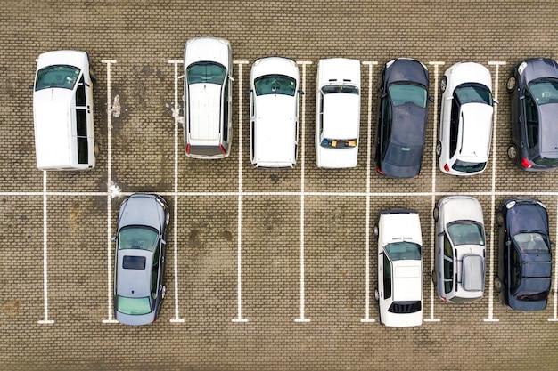 Vista aerea dall'alto verso il basso di molte auto in un parcheggio di un supermercato o in vendita sul mercato del concessionario di auto.