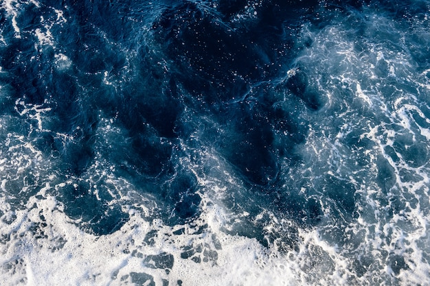 Vista dall'alto in basso della superficie dell'acqua di mare. la schiuma bianca ondeggia la struttura come sfondo naturale.