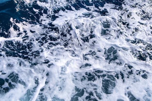 Vista aerea dall'alto verso il basso della superficie dell'acqua di mare. la schiuma bianca ondeggia la struttura come parete naturale.