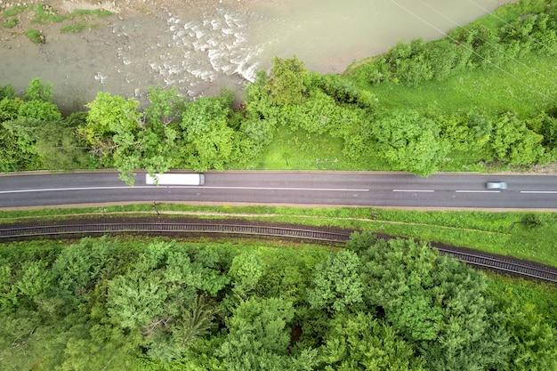 Vista aerea dall'alto verso il basso della tortuosa strada forestale in boschi di abete rosso di montagna verde