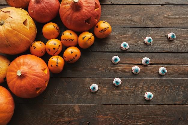 Composizione piatta top-down di zucche intagliate, mandarini con facce di jack o 'lantern e spaventose caramelle a bulbo oculare giacenti sul tavolo di legno