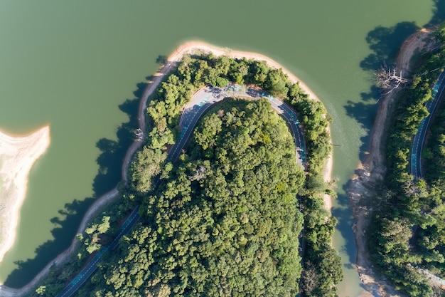 Dall'alto verso il basso dalla vista aerea di drone della foresta pluviale con strada asfaltata intorno alla diga e terreno condiviso, attenzione al cartello della bici su strada.