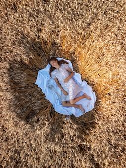 Foto dall'alto di una ragazza sdraiata nel campo di segale su un panno bianco. bella ragazza adolescente nel campo di grano maturo