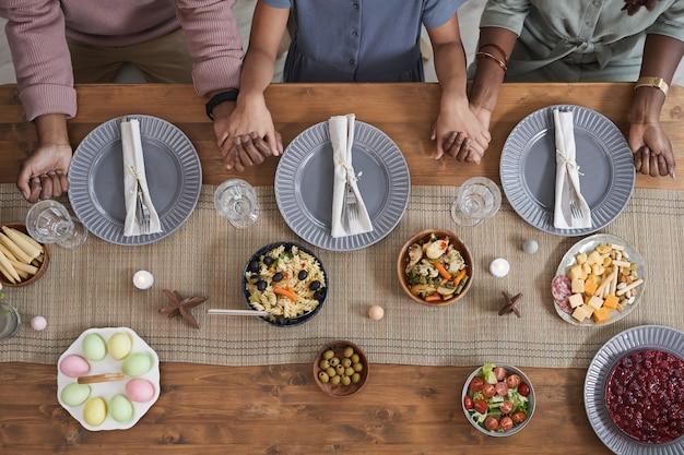Vista dall'alto in basso alla famiglia afro-americana che prega a tavola a pasqua e si tiene per mano, copia spazio