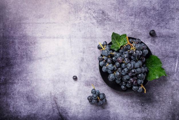 Vista dall'alto in basso di un'uva nera con foglie verdi su sfondo scuro, copia spazio per il testo