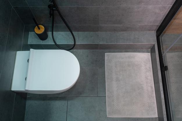 Vista dall'alto su una toilette chiusa con tappetino da bagno e box doccia in un piccolo bagno compatto piastrellato grigio in un appartamento