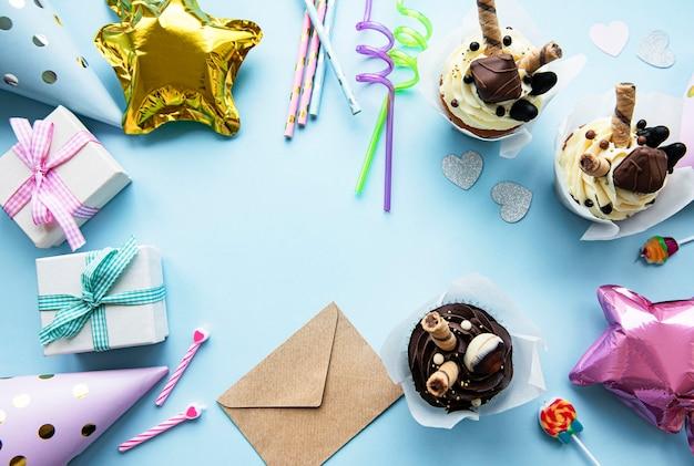 Una vista dall'alto verso il basso di elementi comuni per feste di compleanno in una cornice di confine.