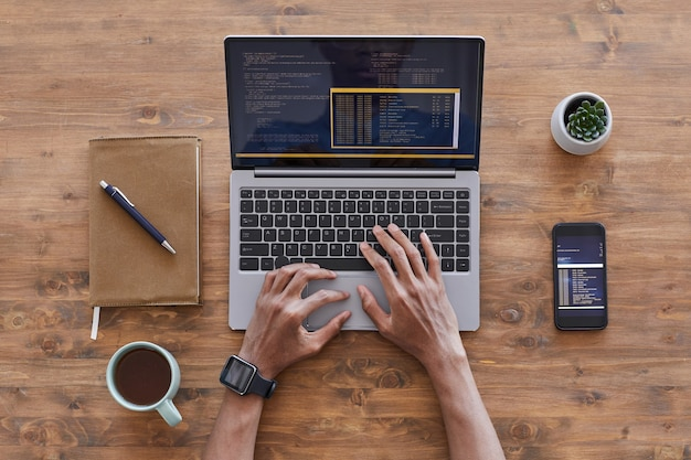 Vista dall'alto in basso alle mani maschile che digita sulla tastiera del laptop durante la scrittura del codice alla scrivania in legno strutturato in studio di sviluppo it, copia dello spazio