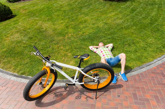 Vista dall'alto in basso sull'uomo rilassante sdraiato sull'erba accanto alla bicicletta con pneumatici grassi gialli e bianchi con spazio per le copie