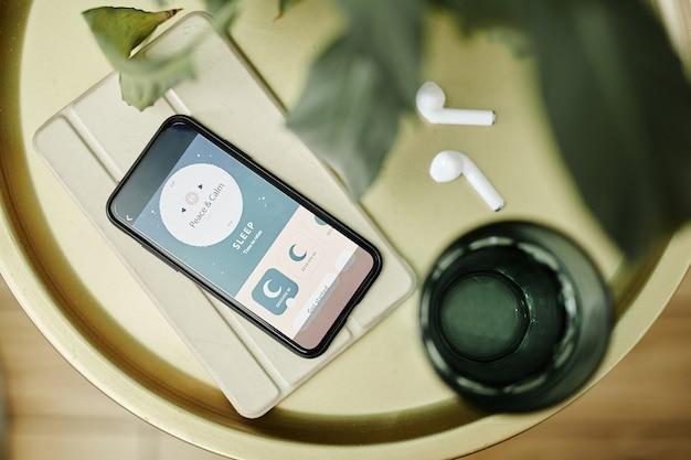 Vista dall'alto verso il basso sullo smartphone con l'app per l'assistente del sonno sullo spazio della copia del comodino