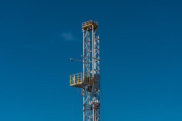 Cima della torre di perforazione con il fondo del cielo blu.