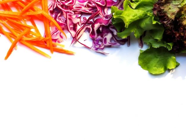 La struttura superiore con l'insalata fresca della verdura fresca pulisce l'alimento delle carote affettate, del cavolo e delle foglie verdi della quercia isolate con lo spazio della copia.