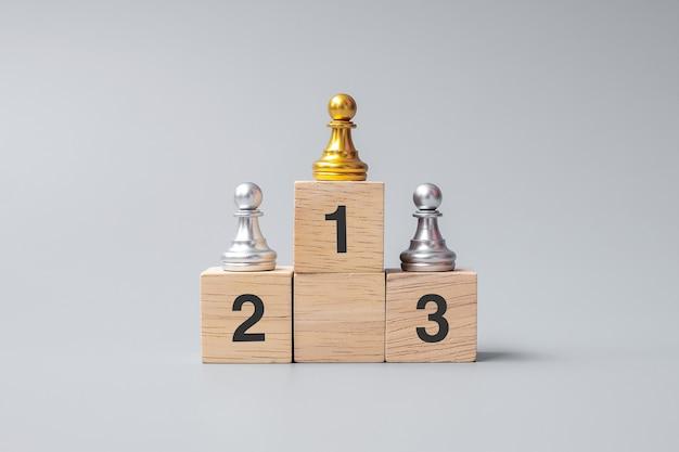 Parte superiore dei pezzi di pedina degli scacchi d'oro o dell'uomo d'affari leader. vittoria, leadership, successo aziendale, squadra, reclutamento e concetto di lavoro di squadra