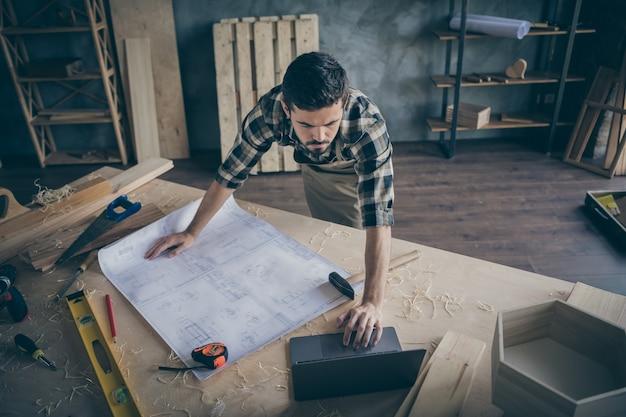 Il lavoratore del legno concentrato sopra ad alto angolo ha una tela con il piano di costruzione dell'edificio usa il computer guarda i video di lavoro manuale nel garage di casa