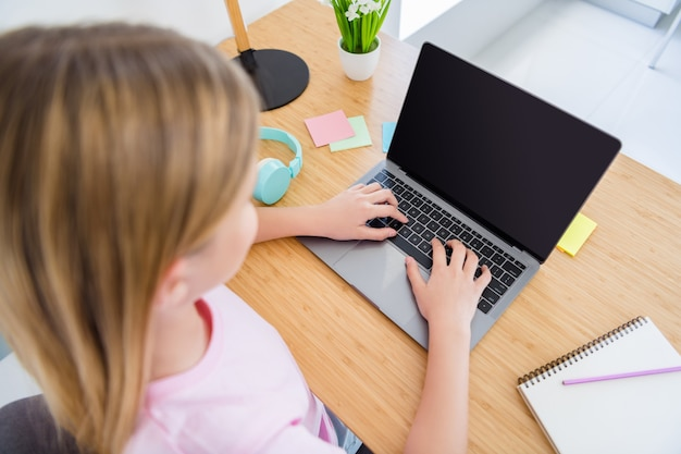 Vista dall'alto dall'alto vista posteriore posteriore vista della colonna vertebrale foto ritagliata di una bambina seduta al tavolo scrivania studio computer per uso remoto avere riunioni online conferenza insegnante in casa al chiuso
