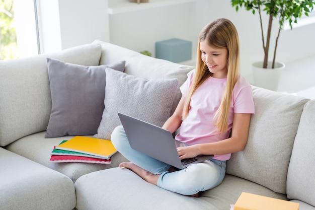 In alto sopra vista dall'alto foto a grandezza naturale di una ragazza intelligente positiva che studia uso remoto laptop guarda video educativi sedersi divano in casa al chiuso