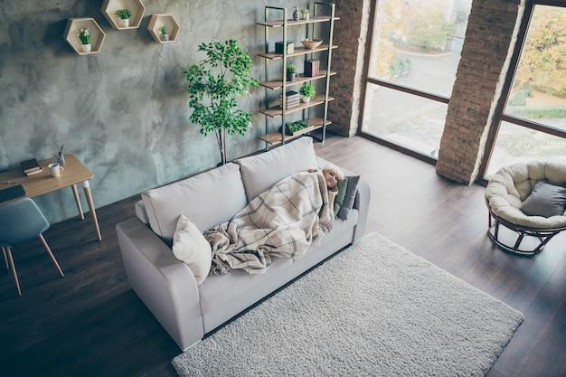 In alto sopra vista ad alto angolo di lei bella nonna di mezza età dai capelli grigi sdraiata sul divano che riposa rilassante ricreazione loft industriale in mattoni stile moderno interni casa appartamento al chiuso