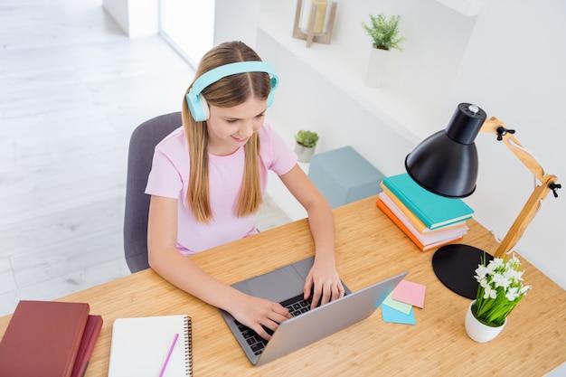 In alto sopra vista dall'alto foto ragazzina ragazza studio uso remoto laptop tipo di testo avere comunicazione online conversazione tutor avere auricolare sedersi comfort accogliente tavolo scrivania in casa al chiuso