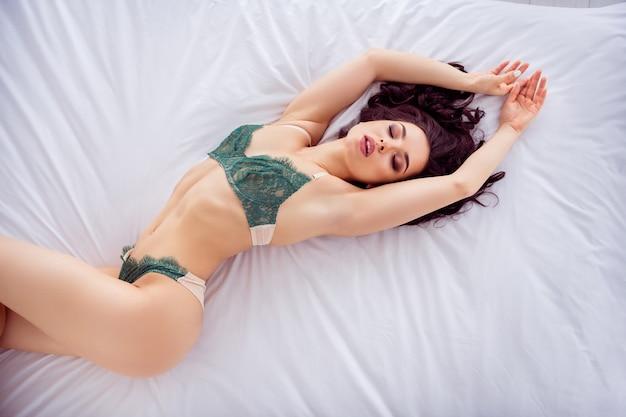 Vista dall'alto in alto ritratto di lei bella vestibilità graziosa sportiva attraente splendida splendida sognante ragazza sdraiata su lino bianco godendo il sonno del pisolino del buongiorno