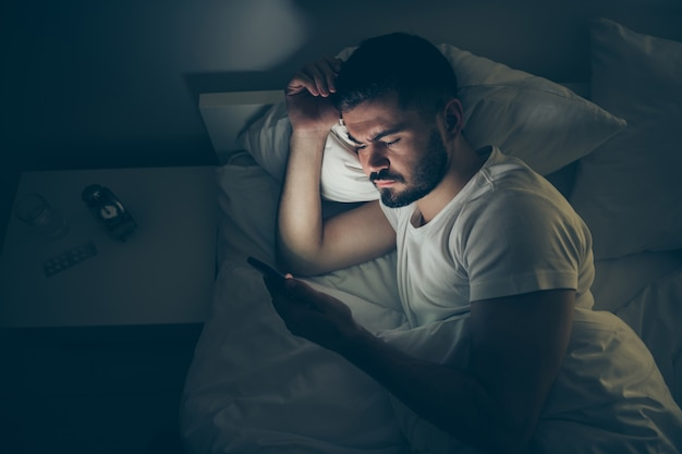 In alto sopra il ritratto di vista ad alto angolo del suo ragazzo bello e attraente concentrato sdraiato a letto utilizzando l'insonnia cellulare digitale di notte a tarda sera casa stanza illuminata scura appartamento casa al chiuso