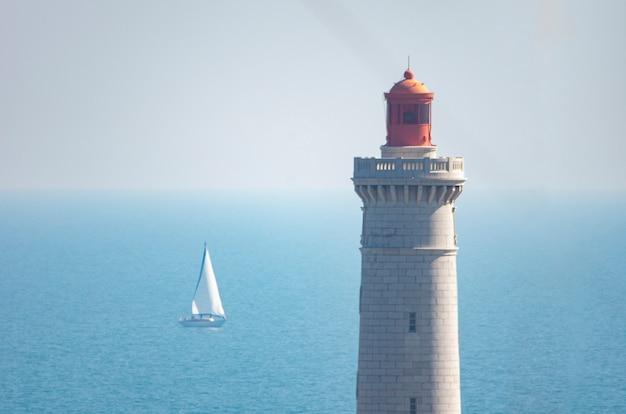 Cima di un faro sul mare con una barca a vela con un cielo limpido