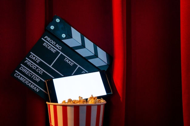 Parte superiore del telefono cellulare con schermo luminoso bianco vuoto sul film di ardesia di film e secchio di popcorn.