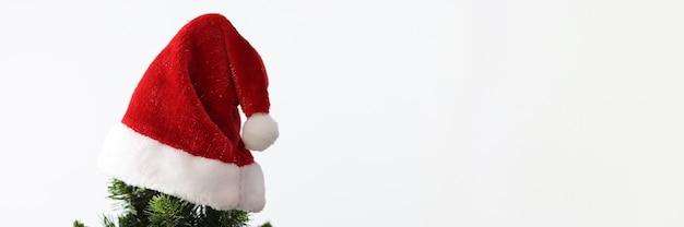 In cima all'albero di capodanno che appende il primo piano del cappello rosso di santa clauss