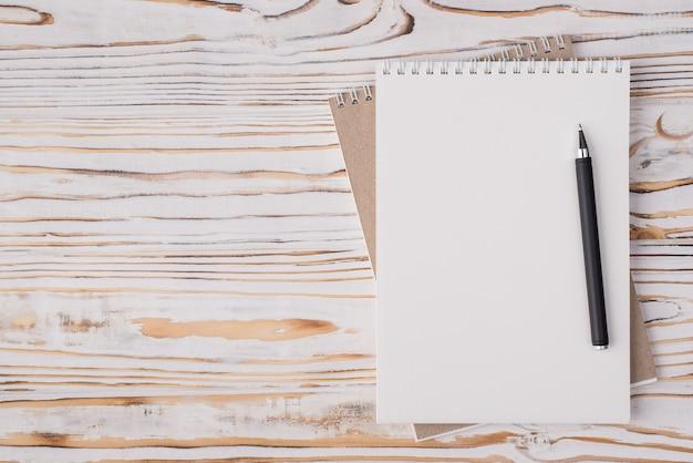Vista dall'alto in alto, foto piatta di un taccuino vuoto e una penna posizionata sul lato destro isolato su sfondo di legno chiaro con copyspace