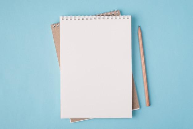 Vista dall'alto in alto, foto piatta di un quaderno bianco e una matita accanto a uno sfondo di colore blu pastello con copyspace
