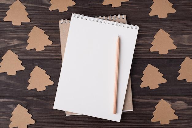 Dall'alto vista dall'alto foto piatta di un quaderno bianco matita e decorazione di carta a forma di albero di natale isolato su sfondo di legno con copyspace