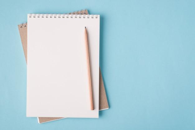 In alto sopra la vista dall'alto foto piatta di un taccuino vuoto e una matita posizionata sul lato sinistro isolato su sfondo di colore blu pastello con copyspace