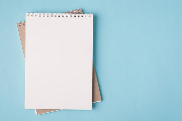 Vista dall'alto in alto, foto piatta di un taccuino vuoto posizionato sul lato sinistro isolato su sfondo di colore blu pastello con copyspace