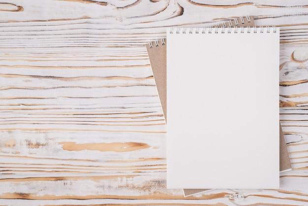 Vista dall'alto in alto, foto piatta di un taccuino vuoto posizionato sul lato destro isolato su sfondo di legno chiaro con copyspace