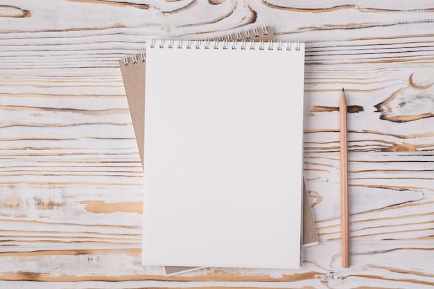 Vista dall'alto sopra la foto piatta di un quaderno bianco e una matita di legno accanto a uno sfondo di legno chiaro con copyspace