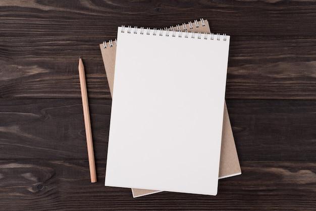 Vista dall'alto in alto, foto piatta di un taccuino vuoto e matita di legno accanto isolato su sfondo di legno con copyspace