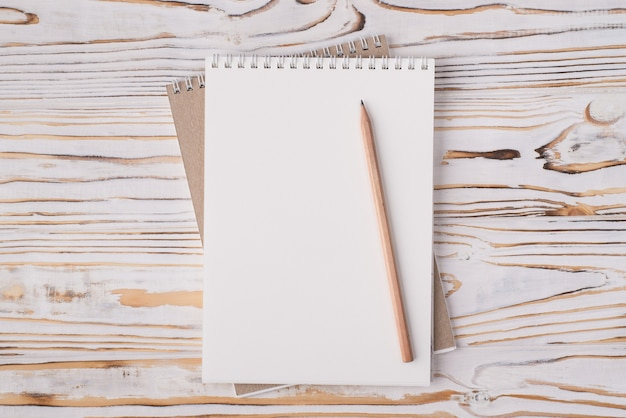 Vista dall'alto sopra la foto piatta di un quaderno bianco e una matita di legno isolati su uno sfondo di legno chiaro con copyspace
