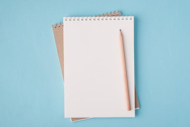 Vista dall'alto sopra la foto piatta di un quaderno bianco e una matita di legno isolati su uno sfondo di colore blu pastello con copyspace