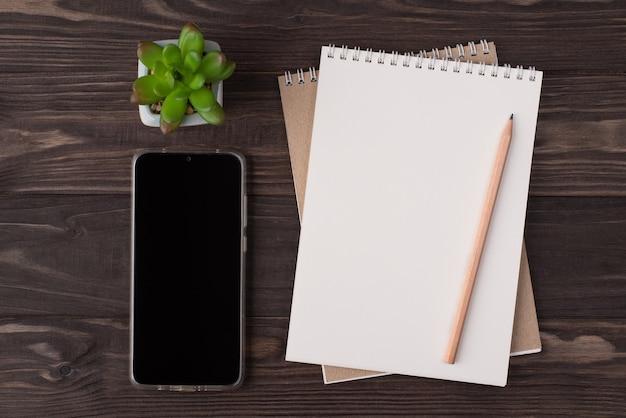 In alto sopra la vista dall'alto foto piatta di un taccuino bianco telefono a matita in legno e succulento isolato su sfondo di legno con copyspace