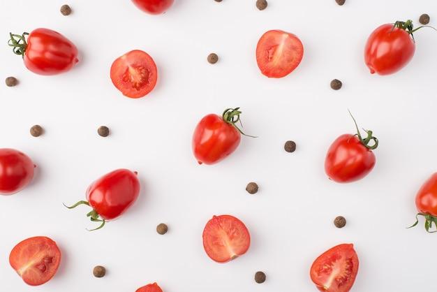 In alto sopra la foto vista dall'alto di pomodorini e grani di pepe isolati su sfondo bianco